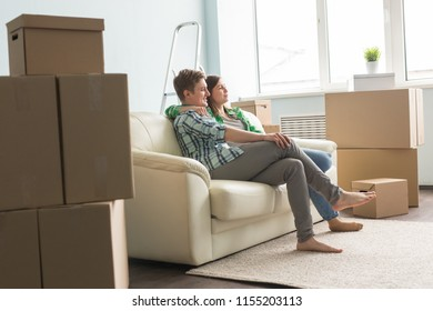 Moving, new things, people concept - happy couple in love sitting in an empty apartment among boxes and dream about future