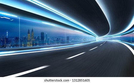 Moving on tunnel with transparent glass window and modern city skyline view .