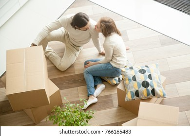 Moving in out, relocation and renovation concept, young happy couple sitting on the floor indoors with cardboard boxes preparing to move, family man and woman packing unpacking belongings, top view