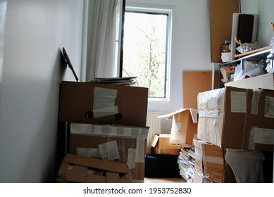 Moving packing concept. Messy Cardboard boxes in a small room with an opened window.