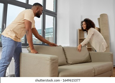 moving, people, repair and real estate concept - happy african american couple with sofa at new home