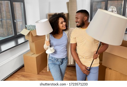 moving, people, repair and real estate concept - happy african american couple with lamps packing stuff into cardboard boxes at home