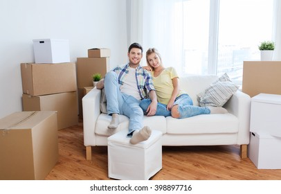 moving, people, repair and real estate concept - happy couple with big cardboard boxes on sofa at new home