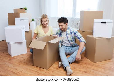 moving, people, repair and real estate concept - smiling couple looking into big cardboard box at new home