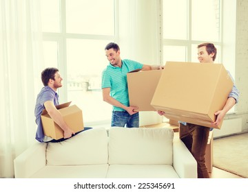 moving, real estate and friendship concept - smiling male friends carrying boxes at new place