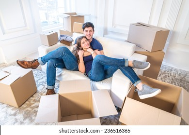 Moving, repairs, new flat. Couple in love hugging lying down and looking at the camera to move and wife hugging her husband while man and woman lying on the sofa among the boxes in an empty apartment