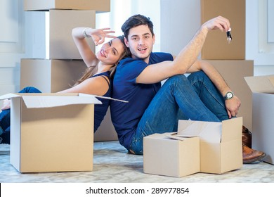 Moving, repairs, new keys to the apartment. Couple girl and the guy holding the keys to the apartment while man and woman sitting on the floor among the boxes in an empty apartment