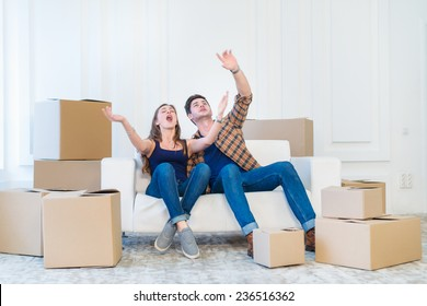Moving, repairs, new life. Couple in love enjoys a new apartment and keep the box in his hands while young and beautiful couple in love sitting on the couch in an empty apartment among boxes