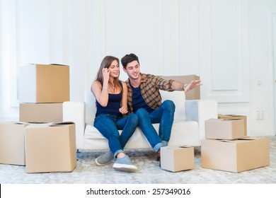 Moving, repairs, new life. Couple in love enjoys a new apartment and keep the boxes near them while young and beautiful couple in love sitting on the couch in an empty apartment among boxes