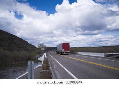 Moving semi truck with the load in a dry van trailer with red doors on the divided lanes road pass over bridge over a small river that crosses the highway in Idaho.