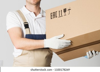 moving service worker holds cardboard box close-up. Mover in uniform holding parcel in hands. Relocation services man. Loader with box on gray background