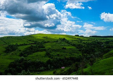moving shadows over green meadows and hills with shrubs, bushes, trees and blue sky white clouds in the spring / East European scenery - Transylvania region / lights and shadows