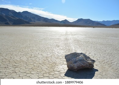 moving stone on the Racetrack Playa leaving tracks in the dry and cracked terrain in the Death Valley National Park, recflections of the sun
