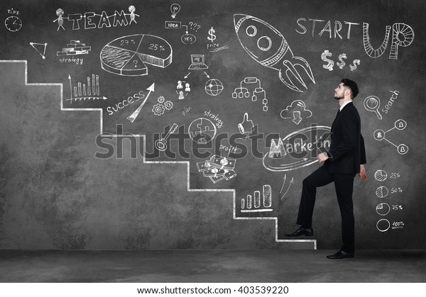 Moving up to success. Full length of confident young man in full suit moving up by illustrated steps and against a concrete wall