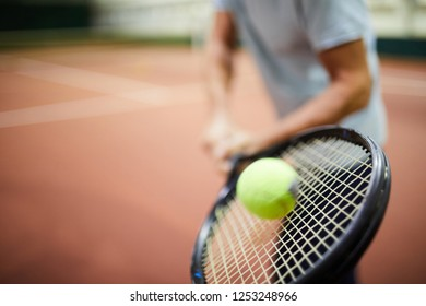 Moving tennis ball being hit by racket in hand of professional player during game