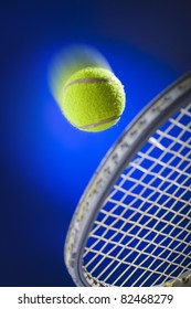 Moving tennis ball just about to be hit from the tennis racket  on blue background
