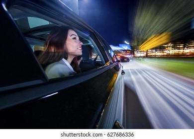 Moving towards the nightlife in the city, woman on the backseat of a car