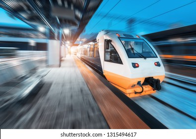 Moving train on the railway station at night. Urban landscape with modern high speed train in motion on the railway platform with illumination at dusk. Intercity vehicle. Passenger railroad travel