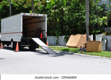 A Moving Van On Street With Ramp, Boxes And Household Furnishings
