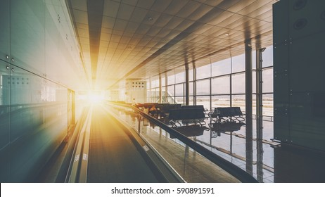 Moving walkway in modern airport terminal, travelator in waiting hall with empty seats, huge windows and reflective floor and walls, flare in the end of route