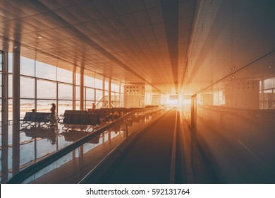 Moving walkway in modern airport terminal of Barcelona, travelator in waiting hall with empty seats and several people waiting their aircraft, big windows and reflective floor, flare in the end of way