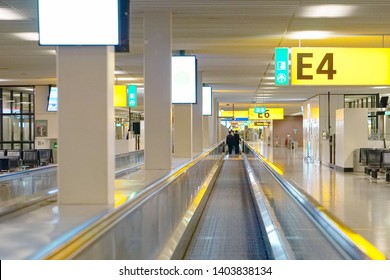 Moving walkway, moving sidewalk, moving pavement, autopedescalator, walkalator, travelator, horizontal escalator, slidewalk, or moveator at an airport.