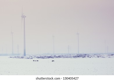 Moving wind turbine  in snow covered winter field and animals on the field