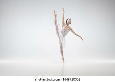 Moving. Young graceful classic ballerina dancing on white studio background. Woman in tender clothes like a white swan. The grace, artist, movement, action and motion concept. Looks weightless.