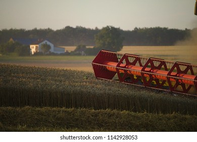 Mower from a combine harvester with a farm in the background