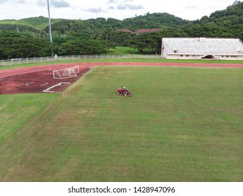 Mower cutting grass at soccer or football field in stadium