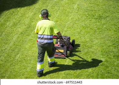 mower lawnmower  and gardener cutting the grass ,  utility worker  in city park