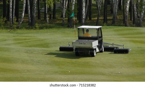 mower work in the grass at the edge of a Scottish golf course. Machine for turf on Golf