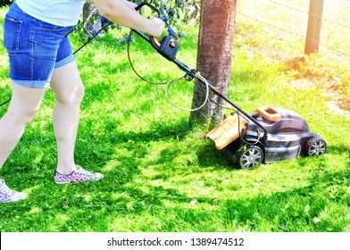 Mowing or cutting the long grass with a  lawn mower in the summer sun. Woman working in garden cutting grass with lawn mower.