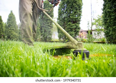 Mowing the grass with a lawn mower. Garden work concept background.