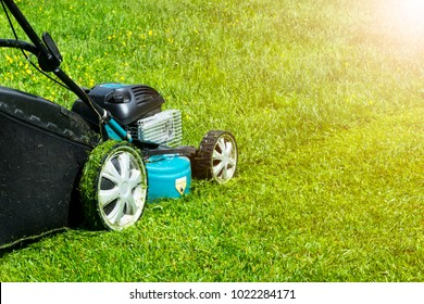 Mowing lawns. Lawn mower on green grass. mower grass equipment. mowing gardener care work tool close up view sunny day. Soft Lightning
