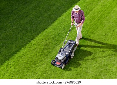 Mowing senior man with straw hat in the garden