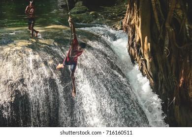 MOYO ISLAND, INDONESIA - JUNE 30, 2014: Local kids playing at a waterfall in Moyo Island