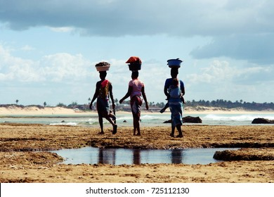Mozambique women carrying basket on the head and baby behind the back walking home after looked for mussels at Tofo beach, Mozambique