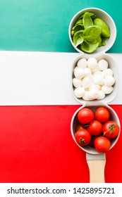 Mozarella cheese balls, fresh basil leaves and  round cherry tomatoes,  forming the italian flag, typical italian food ingredients of mediterranean cusine, top view