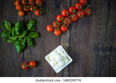 Mozzarella cheese, basil and cherry tomatoes on  brown wooden table. Ingredients for making salad caprese. Mediterranean Kitchen. Soft focus.