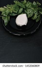 Mozzarella cheese and basil on dark stone background, top view, copyspace. Traditional Italian Caprese Salad, italian mediterranean food.