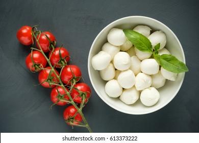 Mozzarella cheese, basil and tomatoes cherry on a gray background. Italian food. Top view.