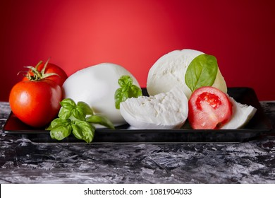 Mozzarella cheese with fresh tomatoes and basil on black and red background.
