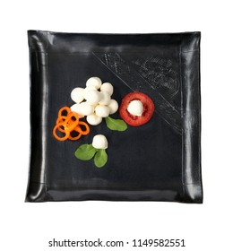 Mozzarella cheese on black square plate isolated on white background