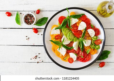 Mozzarella cheese, tomatoes and basil herb leaves in plate on the white wooden table. Caprese salad. Italian food. Top view