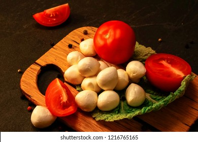 mozzarella cheese with tomatoes on a wooden board, advertising mozzarella cheese, a picture with cheese and tomatoes