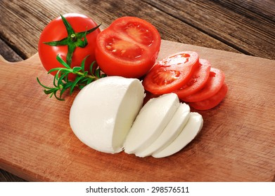 Mozzarella cheese with tomatoes and rosemary on wooden table