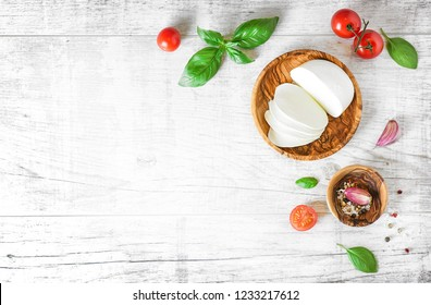 Mozzarella cheese in wooden bowl on white rustic table top view. Soft italian cheeses, tomato and basil on old board with copy space..