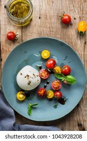 Mozzarella with Cherry Tomato salad on a wooden board