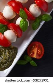 mozzarella with tomato , basil  and pesto sauce on a kitchen table
